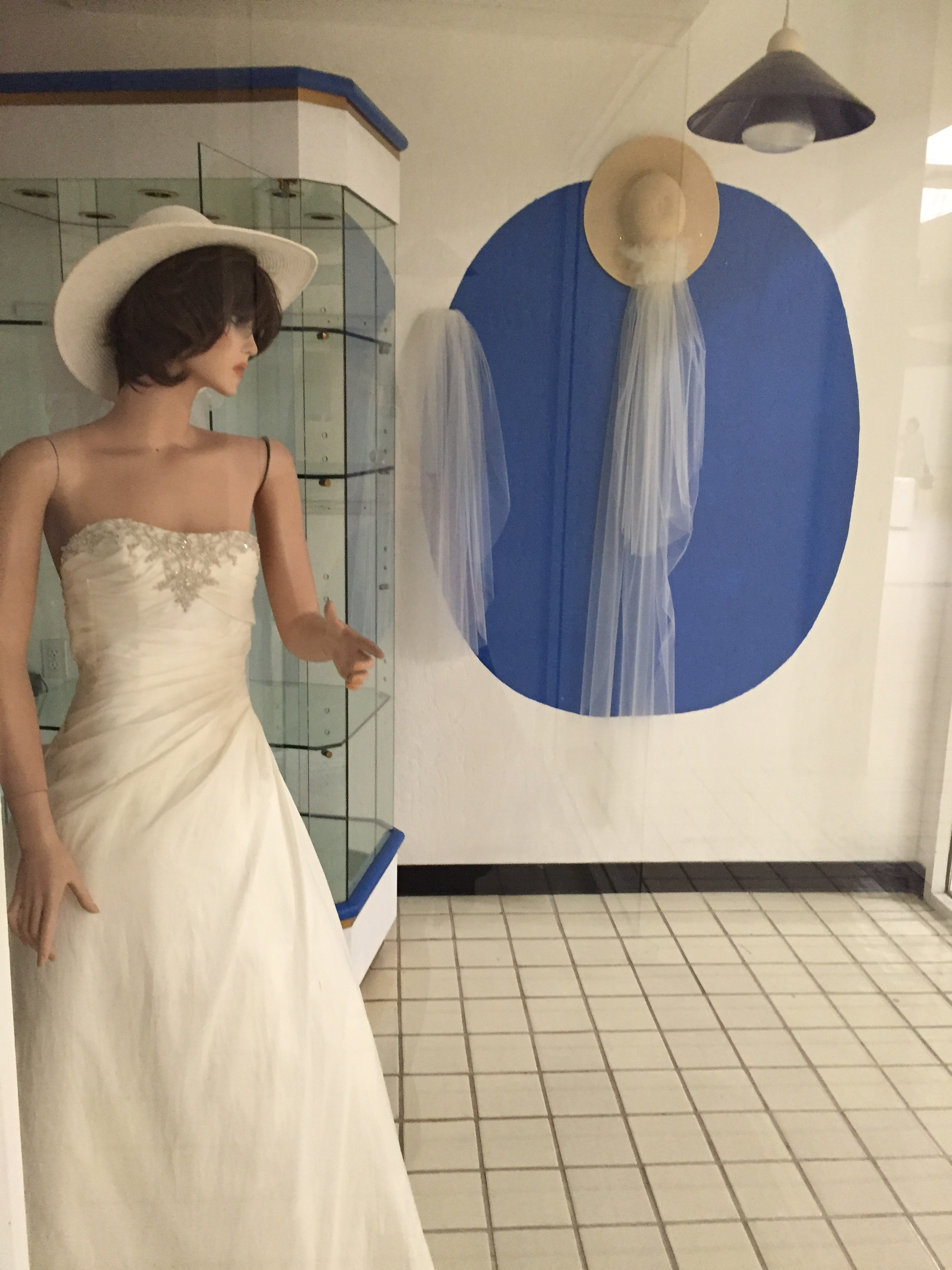 A mannequin in a white sun hat and a wedding gown points at the the viewer, looking away. On the wall behind the mannequin: a display of veils and sunhats.