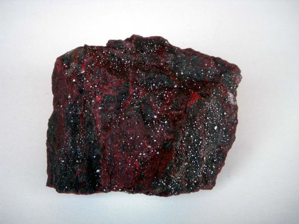 a piece of dark red and black cinnabar sits on a white background.  It's a square shape with rough, lumpy edges.  Small flecks of mercury are visible on its surface.