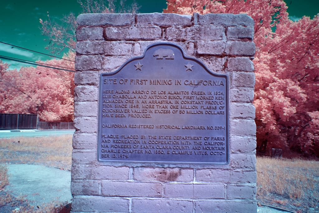 "A color, infrared image shows a current brick monument at the site of the New Almaden Mines.  An aged plaque, with a california bear and two stars on the top reads, ""SITE OF FIRST MINING IN CALIFORNIA: here along Arroyo De Los Alamitos Creek in 1824, Luis Chabolla and Antonio Sunol first worked New Almaden Ore in an Arrastra. in constant production since 1848, more than one million flasks of quicksilver valued in excess of 50 million dollars have been produced.  California registered historical landmark no. 399-1.  Plaque placed by the state department of parks and recreation in cooperation with the california pioneers of santa clara county and mountain charlie chapter no. 1850 E Clampus Vitus, October 13, 1979.""  The brick of the monument is a peachy grey. The background shows some grass, a small picket fence on the left side, and some large, bushy trees.  The ground is a light teal and the sky is a dark teal.  The foilage is a light, peachy pink, which makes it look somewhat like cotton candy."