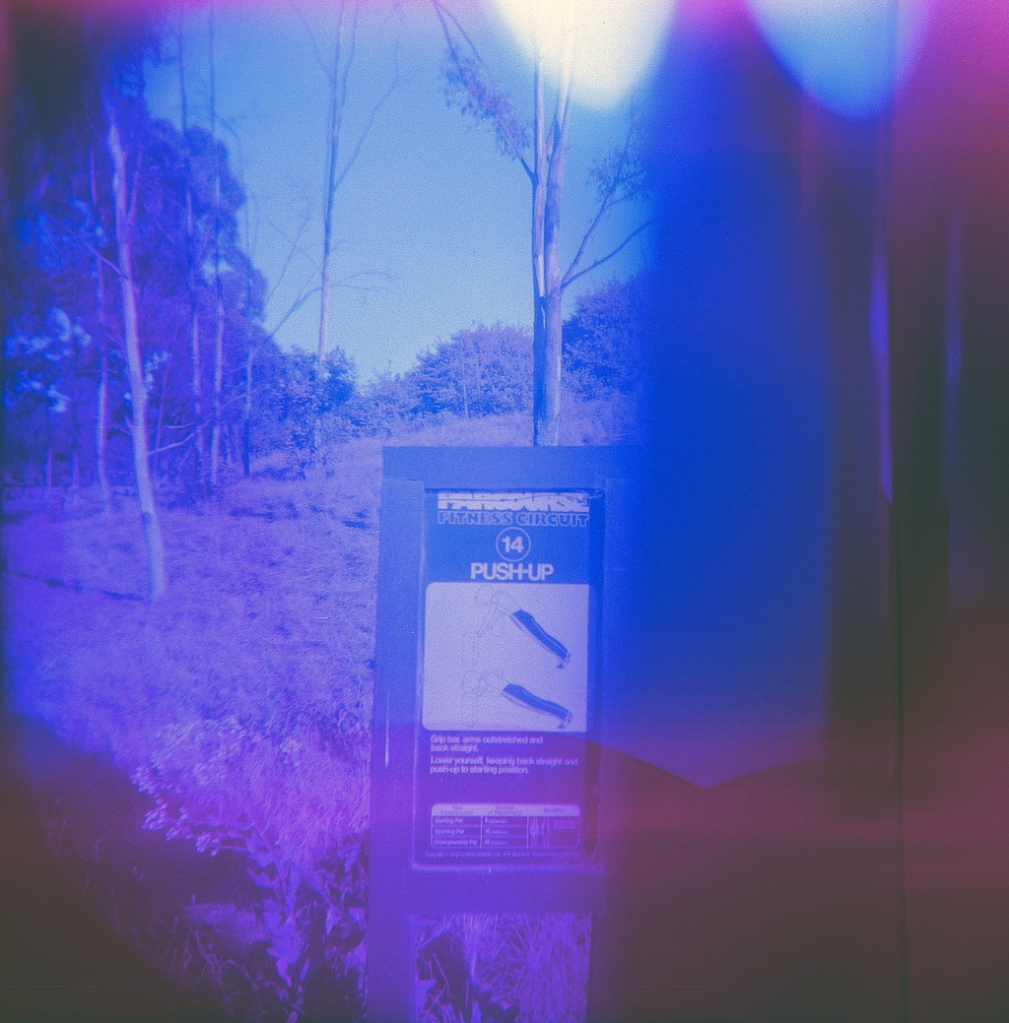 "Two blue and purple hued photographs overlap with one another.  The right side has some hilltops toward the bottom, this part of the image is dark blue and purple, making it hard to discern what the photo is actually of.  The right side of the image shows an old, wooden sign.  It says ""Parcourse fitness circuit, number 14, push-up.""  There are two images of a person doing a push up, and below some unreadable text.  The background shows some sparse trees and a grassy hillside."