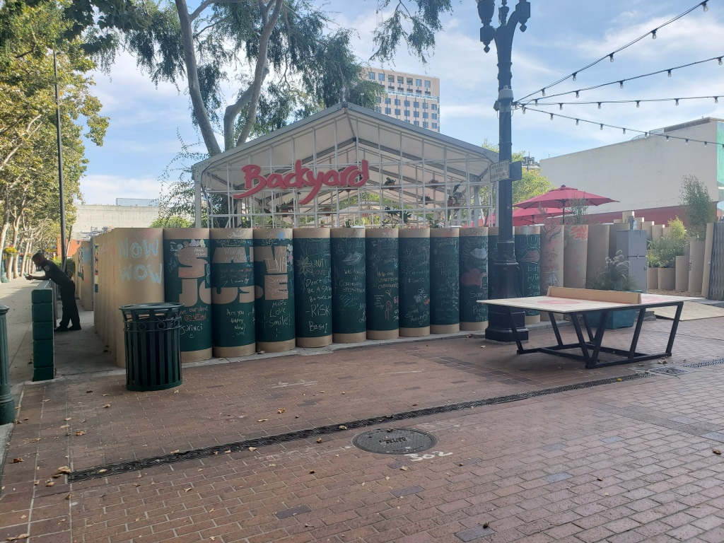 "A photo of Backyard, a pop-up in downtown San Jose's Fountain Alley that took place late summer/early fall of 2019.  The image shows a blue sky in the background, with some large trees on the lefthand side.  A wall-less structure stands at the center of rows of cardboard cylinders.  On the structure is a red sign that reads ""Backyard"".  Some of the cylinders have black chalkboard paint on them, and folks have written messages across most of them.  A set of string lights hover above a ping pong table on the right, and a security guard leans on some fencing on the left."