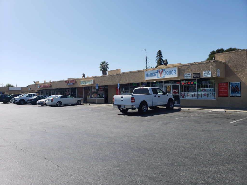 "6 cars are parked outside an small, older strip mall in east san jose.  Closest to us is the Y market.  A white sign with green and red lettering says ""Market Y Liquor.""  The store has white bars on its windows, and a series of advertisements in front of them.  a few trees poke up in the background."