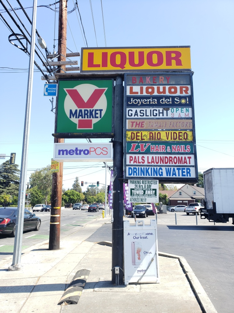"The strip mall's signage sits at the center of the image.  Each store has a unique sign.  The Y market sign is a large square, and a metro pcs sign sits beneath it.  The top sign is a bright yellow and red ""Liquor"" sign, with ""bakery"", ""liquor"", ""Joyeria del Sol"", ""Gaslight open 9 A.M"", The (unreadable) factory"", ""Del Rio Video"", ""LV Hair & Nails"", ""Pals Laundromat"", and ""Drinking Water"".  There is a towing warning sign below and a Metro PCS foldable sign sitting on the ground.  There are cars driving up and down white road in the background and a few trees are visible on the left side."