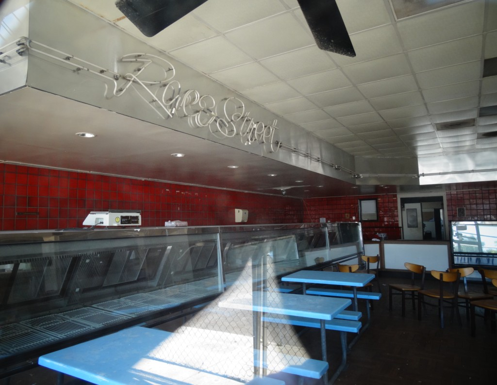 "The image is of the inside of Race Street Fish and Poultry.  A glare from the window sits at the bottom center of the photograph.  Behind it are three blue picnic tables with matching blue bench seating.  A handufull of wooden chairs are strewn about behind them.  The wall is lined with bright red tile, and the seafood storage/presentation areas are all empty.  A white, would-be neon sign reads ""Race Street"" - near the ceiling."