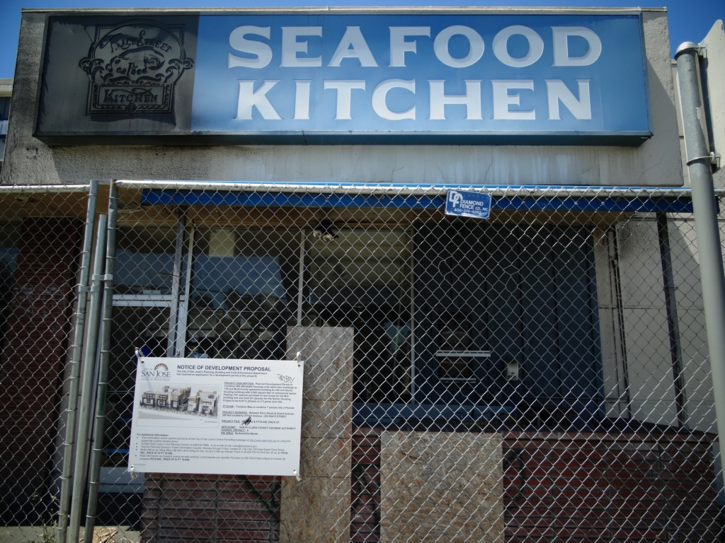 "The image is of the front of Race Street Fish and Poultry.  A large blue sign reads, ""Seafood Kitchen"" and there is a black and grey image to the right that is almost indiscernible. There is an aluminum gate blocking the entrance, and there is some plywood leaned up against it.  There is a white, city of san jose development notice on the front."