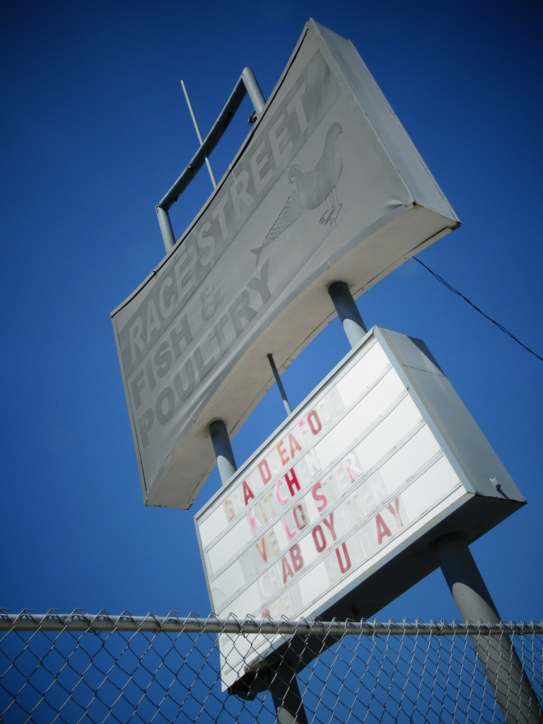 The Race Street Fish and Poultry sign juts up diagonally against a bright blue sky in the background.  The top of the sign is the shape of a bowtie, it is a light grey, and the writing is a darker gray.  There is a fish and chicken on the right side of the sign, they are faded and almost look like one animal. Below is a white marquee sign.  The letters are red, pink, white, and translucent.  The letters spell out g-a-d-e-a-o-h-v-l-i-s-a-b-o-y-u-a-y.