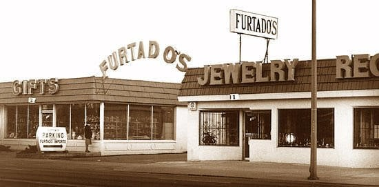 "An old, sepia photograph shows Furtado's store on East Santa Clara street in San Jose.  A small shop on the left has a large sign that reads ""Gifts"", and some items can be seen in the windows.  A parking sign with a large black arrow sits in front of the shop, and a potential customer eyes the goods through the shop window.  An an arched sign that reads ""Furtado's"" connects the gift shop to the jewelry shop next door.  The jewlwery shop has bars on the windows and a smaller, black and white Furtado's sign on its roof.  A sliver of the empty street is at the base of the photograph and a pole juts up on the right hand side."
