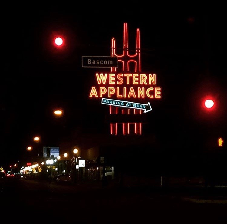 Nighttime on San Carlos Avenue.  The Western Appliance sign glows orange visibly in the foreground.  Cutting through it is the Bascom avenue street sign, probably illuminated by oncoming traffic.  There are various streetlights lining San Carlos avenue, and some breaklights in the distance. On the right of the image is an orange hand, signaling for those waiting to walk across the cross walk.  Two red lights sit to the right and left of the Western Appliance sign.