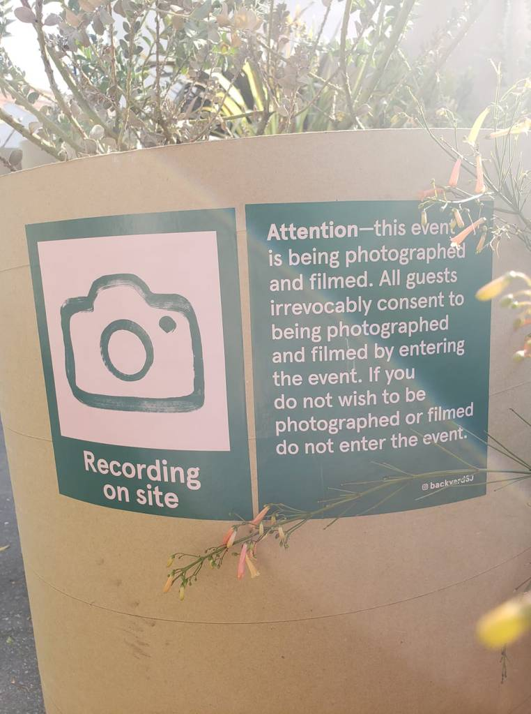 "A short brown cylinder at the exit of Backyard.  It has two dark green signs on it.  In pink writing one says, ""Attention - this event is being photographed and filmed.  All guests irrevocably consent to being photographed and filmed by entering the event.  If you do not wish to be photographed or filmed do not enter the event. @backyardSJ.""  The second sign has a drawing of a camera with the words ""Recording on site"" underneath.  A wildflower pokes into the right side of the image."