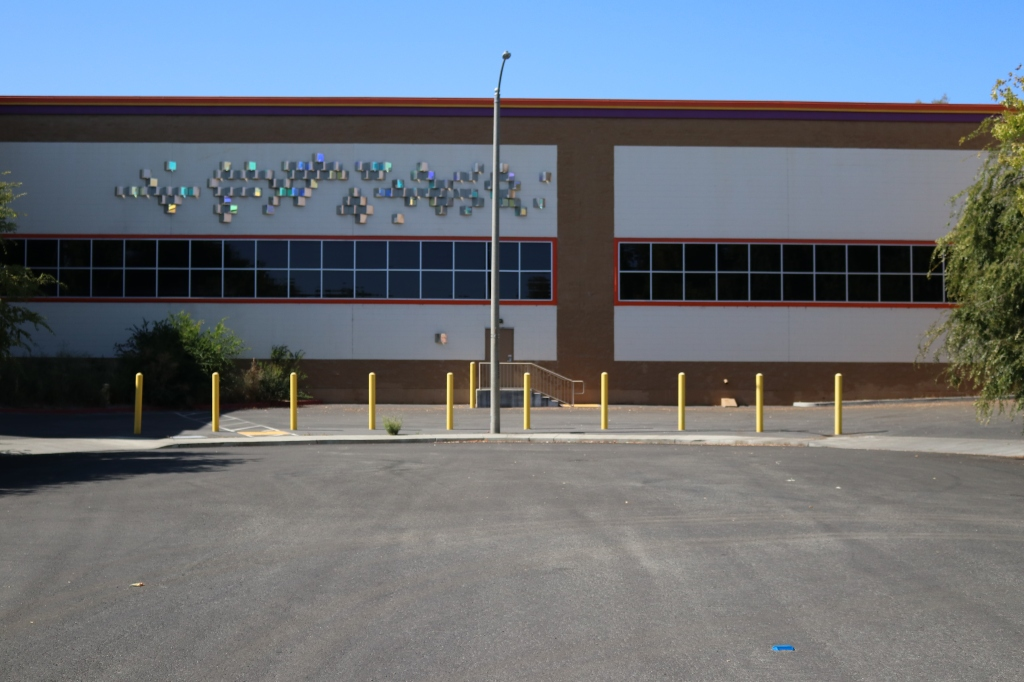 a side view of the Public Storage.  The foreground is a street cul-de-sac, with tree shadows on the left side.  In the center of the photo is some short polls that keep drivers from using this area as an entrance to Public Storage.  Behind the polls is the Public Storage itself, the roof is lined with a purple, yellow, and orange strip.  Some decorative metallic squares are on the upper left of the building, below are long, thin windows.  In the center of the building is a door with stairs going down to the cement.  There is a tree on either side of the image.