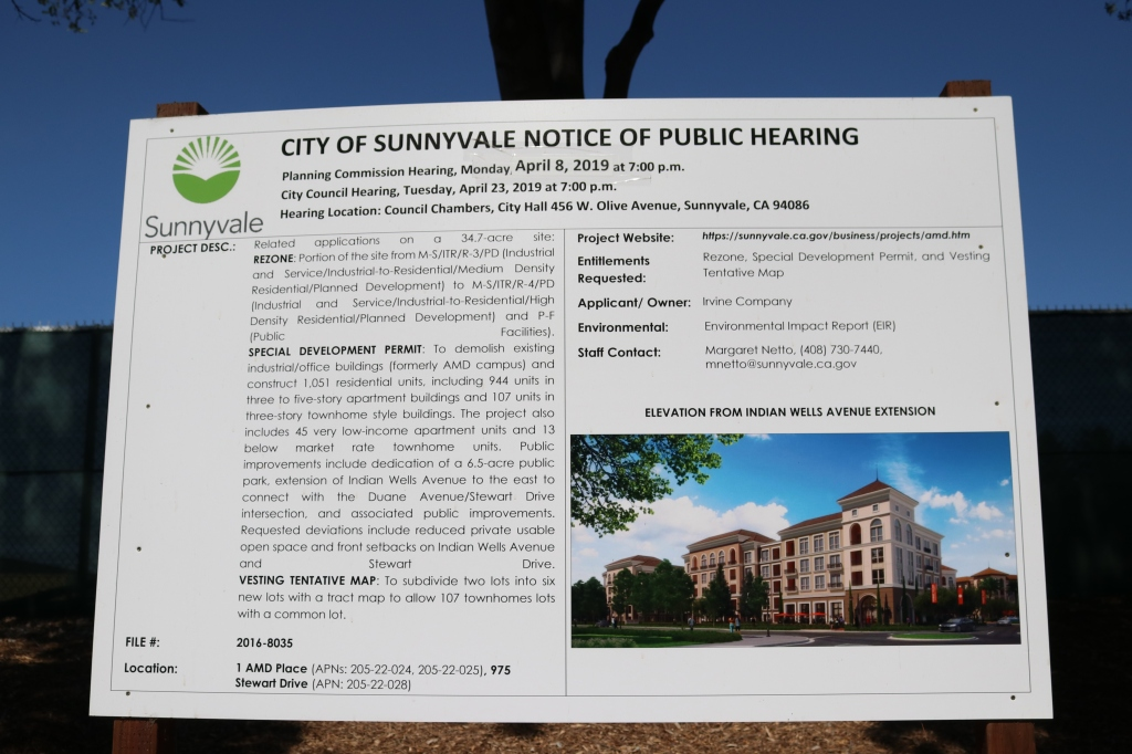 "A ""City of Sunnyvale Notice of Public Hearing"" sign sits in front of a green privacy screen and a blue sky.  On the sign is information from a public hearing that took place on April 8th, 2019.  The bottom right of the sign has an image of the future housing project that will be built in this location.  It is mixed use housing on a tree lined street."