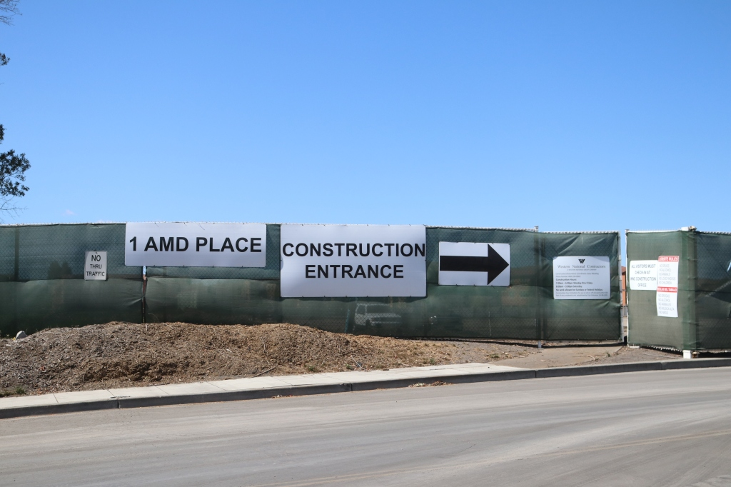 "in the center of the image sits a long chain link fence, covered in a green privacy screen.  On the fence there are 7 signs.  The three large ones are white, with a black arrow, the words ""construction entrance"", and the address (1 AMD Place) written in lagge black letters.  A smaller sign to the left says ""NO THRU TRAFFIC"", the four signs to the right are unreadable.  In the background is the blue sky, with a small tree poking out on the left, the foreground is the street, a sidewalk, and piled dirt."