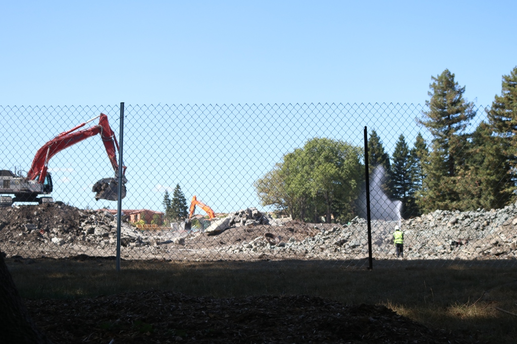 the image shows the debris left after the demolition of Advanced Microwave Devices.  The piles are probably around 15 to 20 feet high, mostly concrete dirt, and rock.  A worker in a bright yellow vest and hardhat hoses the dirt off.  Two tractor scoops are visible, one in the foreground and one in the background.  A housing tract can be seen in the distance.