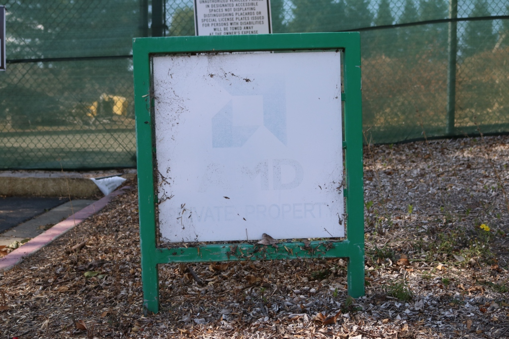 A white sign, with a green frame and legs sits on a leaf ridden dirt patch.  The center of the sign says AMD PRIVATE PROPERTY with the AMD logo, but it is almost completely faded.  Behind the sign is a green privacy screen, there is a white sign with black writing hung on the screen, it is unreadable.