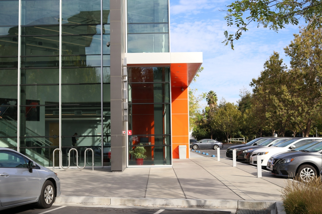 the entrance to small apple campus.  The building is all windows, and the entrance has a slick, bright orange overhang. The parking lot is lined with silver, white, and black cars.  The street is lined with trees and there is an empty bike rack outside.  A person stands inside the glass building, they are wearing a black shirt and looking down at their phone.