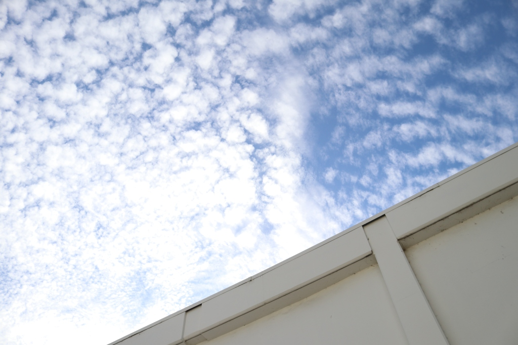 a diagonal photograph shows the upper part of a building roof.  A blue sky takes up the rest of the image, white clouds dot its surface.
