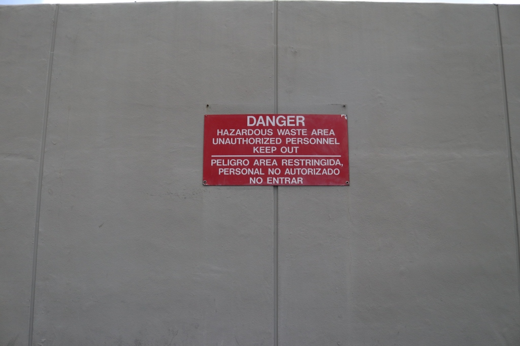 "A red sign is on the side of a grey building, it reads, ""Danger, hazardous waste area unauthorized personnel keep out.  Peligro area restringida personal no authrizado no entrar."""