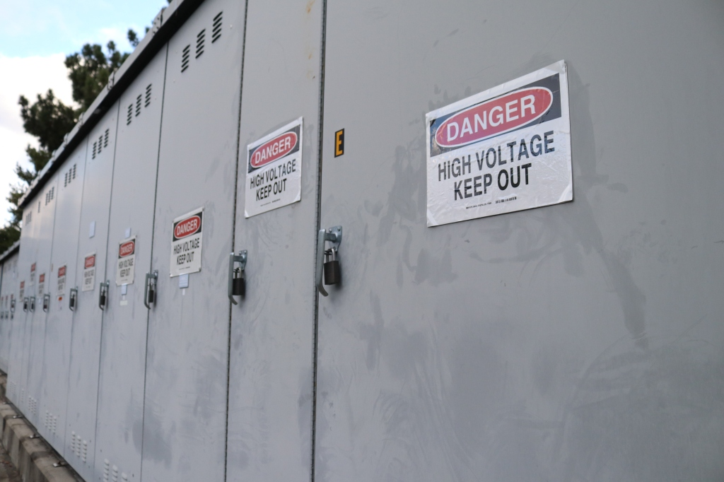 "A series of metal lockers each have a ""Danger, keep out, high voltage."" sign on them."