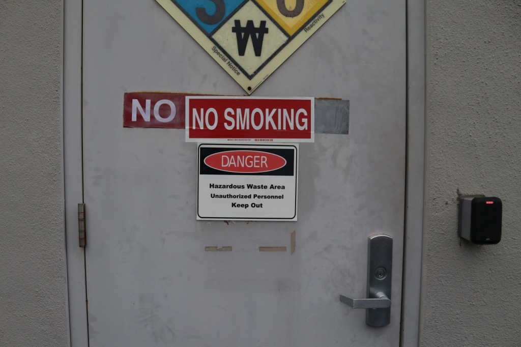 A 'no smoking' sign has been covered by a smaller 'no smoking sign', below it another sign reads, 'Danger, hazardous waste area unauthorized keep out.""