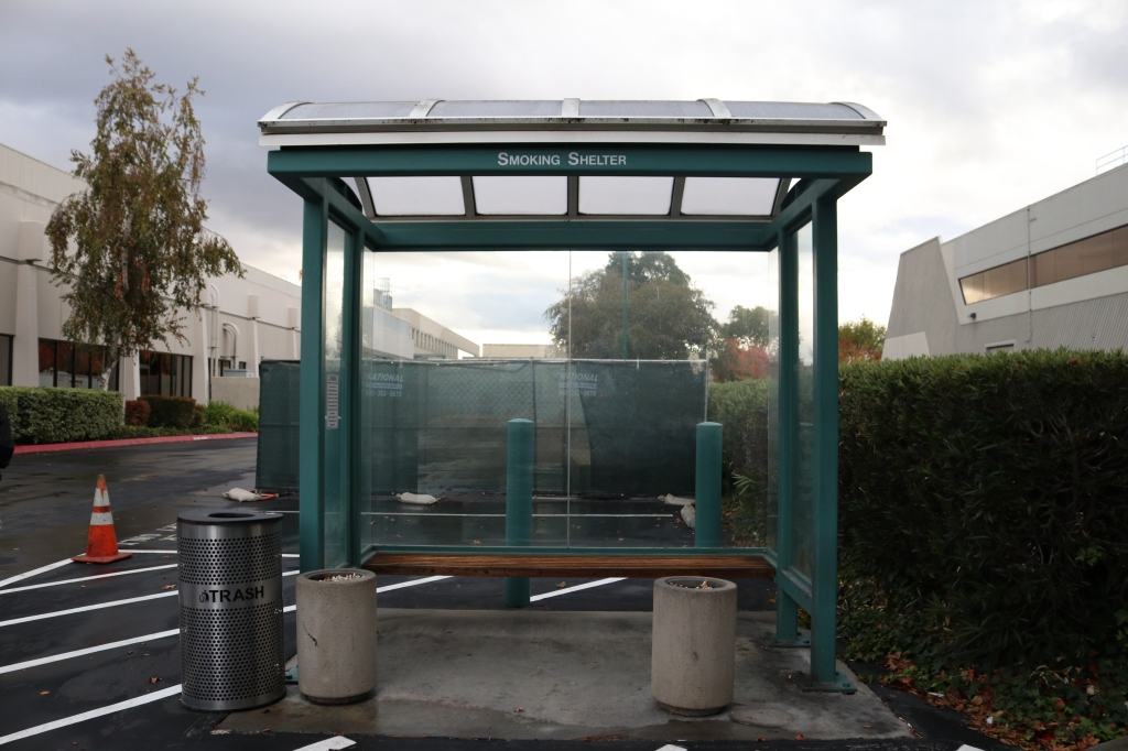Another image of the smoking shelter. This one is slightly cleaner, the trash can isnt overflowing, and there are two ash trays instead of one.