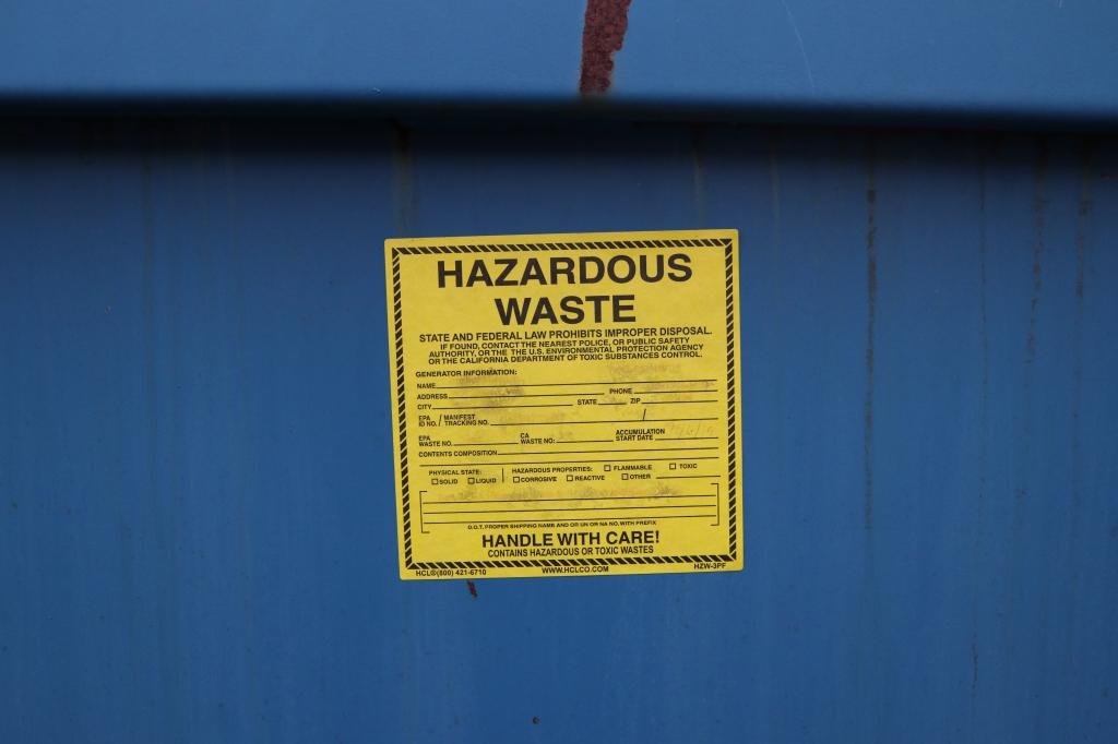 "A blue dumpster has a large yellow sticker on its side.  Not all of the text is visible, and most are supposed to be filled in by someone.  In large letters at the top it reads, ""Hazardous waste.""  The bottom says, ""Handle with care."""