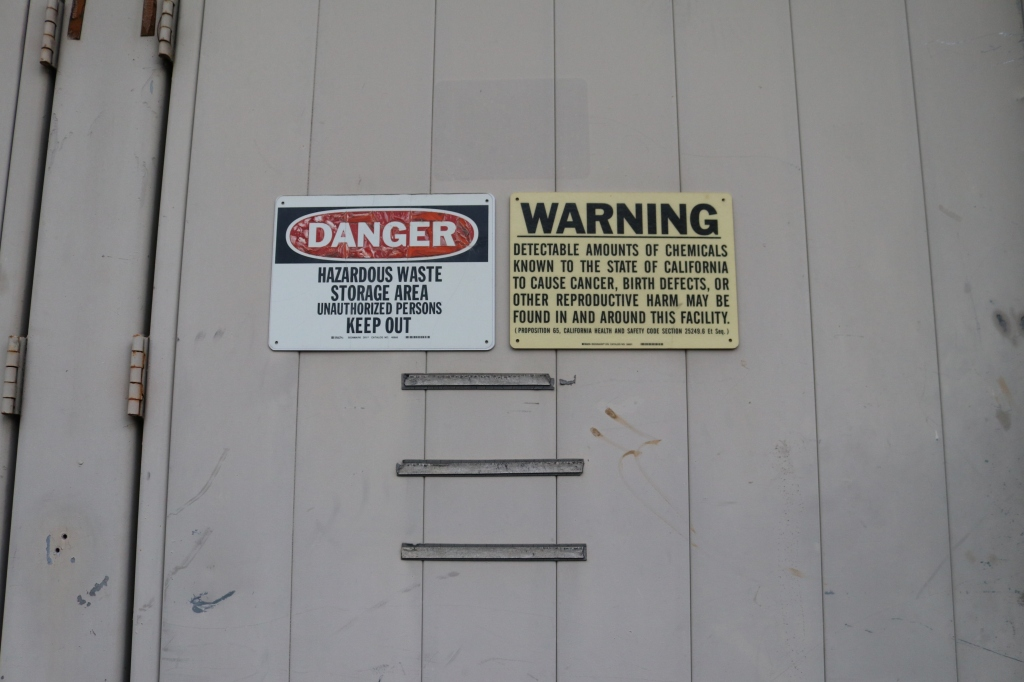 "a white building has two warning sides on it.  One says, ""Danger, hazardous waste storage area unauthorized persons keep out.""  The other says, ""Warning, detectible amounts of chemicals known to the state of california to cause cancer, birth defects, or other reproductive harm may be found in and around this facility."""