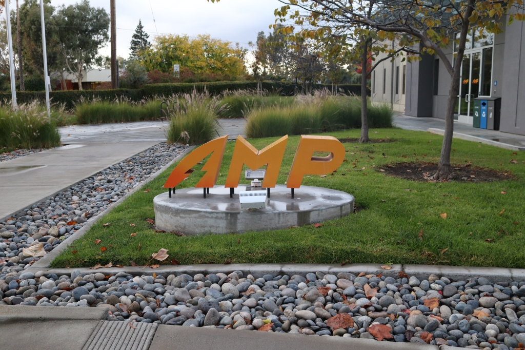 A set of large, orange, and slightly slanted letters spell out A.M.P.  They are surrounded by the manicured outside of a building.  The outside area is damp and grey, it's a rainy day and there are no folks to be seen, just some grass, rocks, and cement.