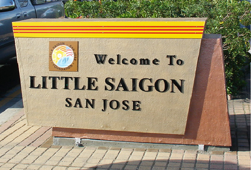 "A sand colored sign, with an elongated Vietnamese flag across the top reads ""Welcome to Little Saigon San Jose."" A smaller logo sits on the left and it says ""Little Saigon, San Jose Foundation."" Behidn the sign is a green shrub and a portion of a blue Toyota Tacoma."