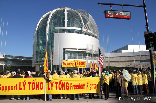 "20 people stand in front of city hall, their backs to the camera.  Most are wearing a light yellow shirt.  City hall is in the background and there are various U.S and Vietnam flags in the foreground.  Two long banners read ""We support Ly Tong."" and another reads, ""Support Ly Tong - Ly Tong Freedom Fighter."""