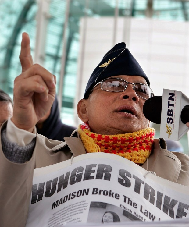"A photograph of hunger striker, Ly Tong.  The image is looking up at Ly, he is speaking into a microphone and pointing up toward the sky with the index finger on his left hand.  He is wearing a military style hat, sunglasses, and a yellow and red scarf.  He has a enlarged newspaper clipping hanging from a string around his neck.  In large, bold letters on the top it reads, ""Hunger Strike."", below ""MADISON broke the law."""